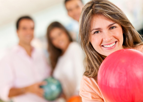 Smiling female Bowler holding red bowling ball