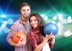 Happy couple bowling with light show