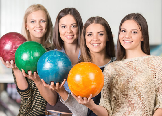 Four smiling women hoding brightly colored bowling balls