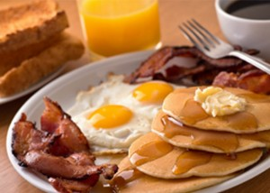 Breakfast with eggs, bacon, pancakes, toast, orange juice and coffee